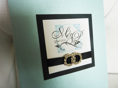 Invitation 915: Blue Aspire Pearl, Black Linen, White Smooth, Devon, Copperplate, Black Ribbon, Brooch/Buckle C