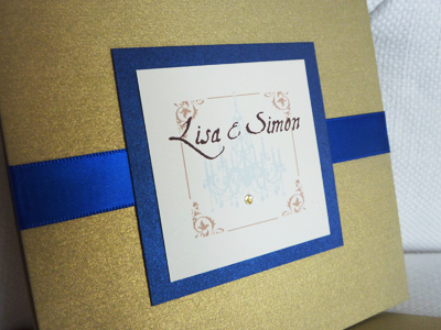 Invitation 932: Gold Pearl, Royal Blue Pearl, Cream Smooth, Aqualine 2, Calligraph 421, Royal Blue Ribbon, Brooch/Buckle Rhinestone