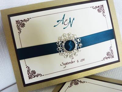 Invitation 935: Gold Pearl, Chocolate Smooth, Cream Smooth, Aqualine 2, Nuncio, Teal Ribbon, Brooch/Buckle R